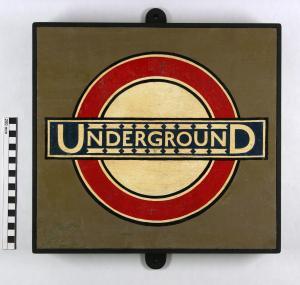 """La imagen muestra una placa metálica de color verdoso sobre la que se ve el círculo rojo atravesado por el rectángulo azul sobre el que está escrito la palabra """"Underground"""". Pulse para ampliar."""