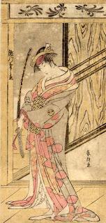 La imagen muestra a una mujer vestida con un largo kimono gris estampado con flores rojas. Está de pie, en medio de una habitación de la que sólo se aprecia una pared del fondo y el suelo, ambos de madera. En su mano parece llevar una rama. Pulse para ampliar.