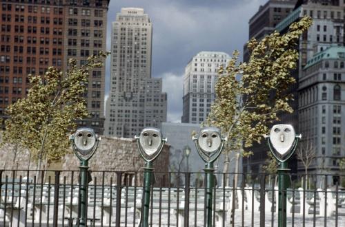 la imagen muestra una calle de la ciudad. En primer plano, cuatro binoculares de los utilizados para ver las vistas panorámicas y que están sujetos al suelo por un poste. tras ellos aparece una verja y una especie de parque y mas alla el perfil de los rascacielos de la ciudad. Pulse para ampliar