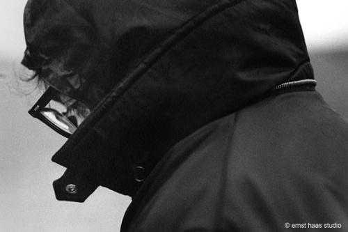 La imagen muestra un primerísimo plano del director y actor de cine Woody Allen. Está abrigado con un impermeable oscuro y lleva una capucha, de modo que lo único que se parecía de su rostro son sus gafas y sus ojos. Pulse para ampliar.