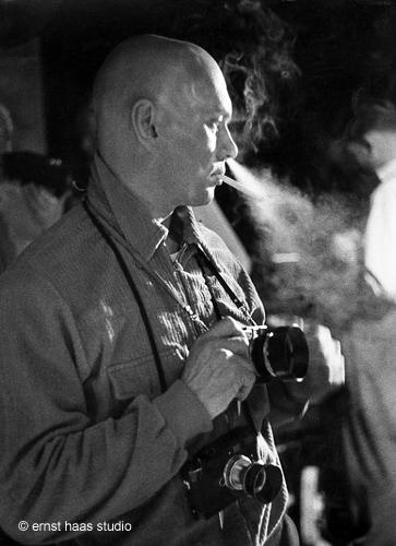 La imagen muestra al actor Yul Brynner en un plano medio -hasta la cintura- de perfil, mirando hacia la derecha e iluminado desde el fondo, lo que hace que su perfil se resalte. Está fumando un cigarrillo y expulsa el humo por la nariz con una mirada pensativa. lleva colgada del cuello por una correa una cámara de fotos. Pulse para ampliar.