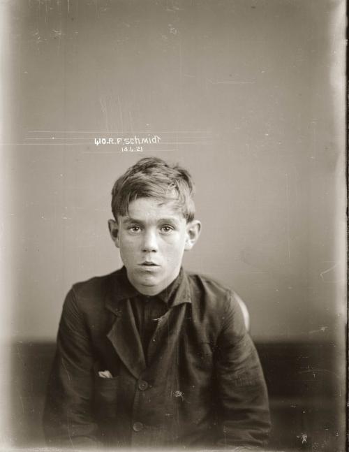 Ronald es un chico de unos 13 años. La fotografía le muestra en plano medio (hasta la cintura). Lleva una camisa negra y una chaqueta sucia y remendada encima. Tiene el pelo corto y rubio y mira a la cámara con un cierto miedo. Pulse para ampliar.