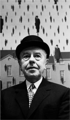 """La imagen muestra una fotografía en primer plano del pintor. Viste traje negro, camisa blanca y corbata a cuadros. Lleva un sombrero hongo y posa delante de su cuadro """"Golconda"""" donde aparecen pintados muchos hombrecillos vestidos igual que el. Pulse para ampliar."""