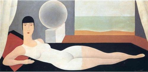La imagen muestra a una mujer tumbada sobre una especie de divan. Lleva un bañador blanco que le cubre parte de los muslos. Está en un interior porque se aprecian pare de unos cortinajes y sin embargo, al fondo del encuadre se aprecia una abertura, como si esa casa no tuviera pared, a través de la cual se ve el mar. Pulse para ampliar.