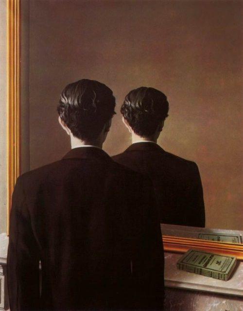 La imagen muestra a un hombre en plano medio de espaldas al espectador y frente a un espejo. En el espejo se ve reflejado el hombre pero tal y como lo vemos nosotros, es decir, de espaldas y no de frente como debería corresponder. pulse para ampliar.