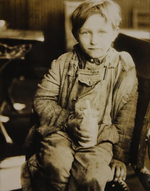 La imagen muestra a un niño pequeño, de unos 7 años, vestido muy pobremente, con un jersey deshilachado y un pantalón de peto sucio y roto. Está sentado en una silla y en su mano derecha sostiene una botella pequeña de cristal vacía de la que asoma una cuchara. Mira hacia el fotógrafo con rostro serio pero mirada risueña. Pulse para ampliar.