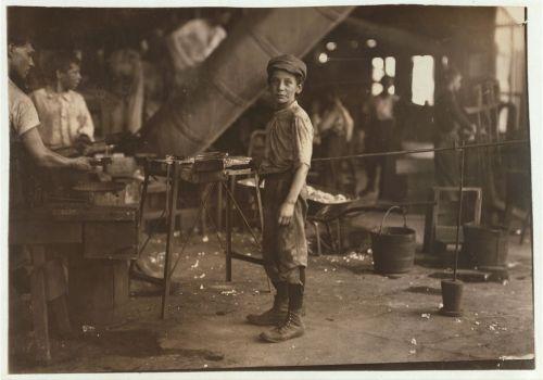 La imagen muestra a un niño en medio de una sala en una fábrica, rodeado de cubos y herramientas. Está de pie, de perfil pero ha girado la cabeza y mira hacia el fotógrafo. Pulse para ampliar.