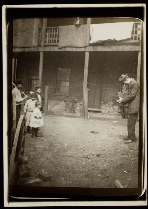 La imagen muestra un callejón sucio en donde, a la derecha del encuadre, aparece Lewis Hine con su cámara, enfocando a un grupo de niños que están mirando hacia él, situados en el lado izquierdo del encuadre. Pulse para ampliar.