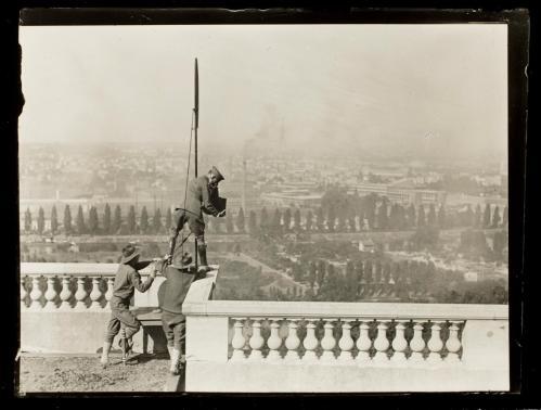 La imagen muestra a Hine subido a una balaustrada de piedra al lado de un mástil de bandera. Enfoca con la cámara hacia abajo -parece estar en una terraza a varios pisos de altura- mientras dos compañeros le sujetan de las piernas. Pulse para ampliar.