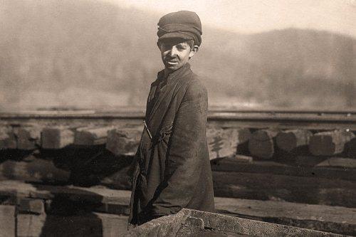 La imagen muestra una fotografía de un plano medio de un niño delante de una vía de tren. Lleva una chaqueta muy grande para él y una gorra cubierta por lo que parece un sombrero de punto. Tiene la parte inferior del rostro lleno de hollín y mira al fotógrafo con cansancio. Pulse para ampliar.