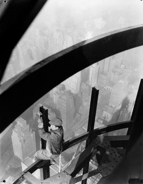 La imagen muestra un plano picado - es decir, visto desde arriba- de un obrero subido a unas vigas de acero que forman la estructura del rascacielos. Está sentado sobre una viga y con las manos manipula otra viga perpendicular. Abajo, a muchos metros, se ve la ciudad de Nueva York y sus edificios más altos, que quedan por debajo de la altura a la que trabaja el obrero. Pulse para ampliar.