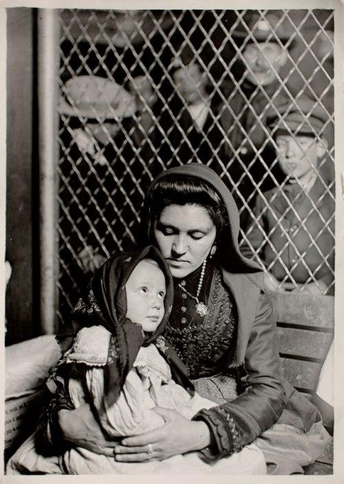 La imagen muestra una fotografía en blanco y negro de una mujer sentada con una nicho en brazos. Ambas están situadas delante de una reja, sentadas en un banco de madera. Están captadas en plano medio, es decir, a la altura de la cintura. La madre rodea con los brazos a la niña que se acurruca en su seno. Ambas se están mirando. Pulse para ampliar.