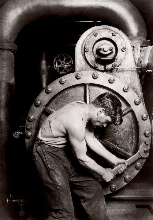La imagen muestra a un hombre que lleva una enorme llave inglesa en las manos, girando uno de los tornillos de una gran rueda metálica perteneciente a una maquina aún mayor. Pulse para ampliar.