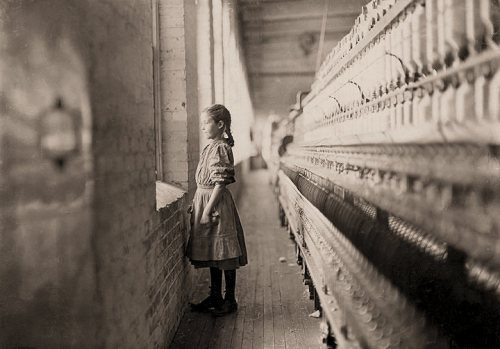 La imagen muestra una vista general de una sala de una fábrica textil. A la derecha y ocupando todo el alto del encuadre, una máquina con bobinas de hilo. A la derecha, una pred con una ventaba. Una niña pequeña, que llega hasta la mitad de altura de la máquina, mira hacia fuera por la ventana mientras la luz exterior le baña el rostro. Pulse para ampliar.
