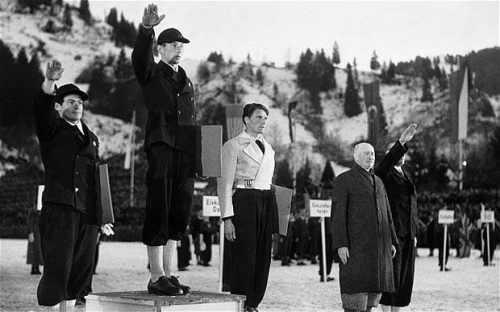 La fotografía muestra el podio de la prueba. Los ganadores del oro y la plata van vestidos de negro y hacen el saludo nazi levantando el brazo derecho. Allais va con una chaqueta blanca y mantiene los brazos pegados al cuerpo. Pulse para ampliar.