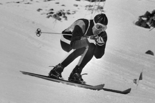 La fotografía muestra al esquiador en pleno descenso, agachado sobre los esquíes y con los bastones recogidos bajo los brazos. Pulse para ampliar.