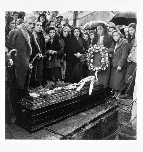 La imagen muestra un ataúd en primer plano y rodeándolo por detrás un grupo de personas. Están abrigadas, llueve (se ven algunos paraguas). En uno de los extremos del ataúd se ve a una mujer joven de pie, compungida, sosteniendo una corona de flores. Pulse para ampliar.