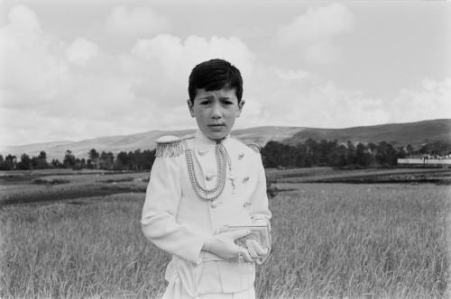 La imagen muestra a un niño con uniforme para la primera comunión, todo de blanco, con guantes y un pequeño misal en las manos. Posa delante de un campo de cereal. Pulse para ampliar.