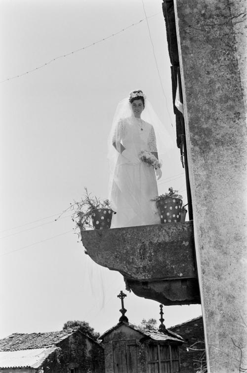 La imagen muestra a una joven vestida de novia en un balcón de piedra, que sólo es la plataforma, sin ningún tipo de pretil. Está fotografiada desde abajo. Pulse para ampliar.