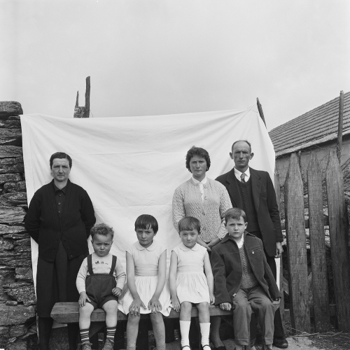 La imagen muestra a un grupo de 7 personas delante de una sábana blanca tendida entre el muro de una casa y un vallado. De pie están una muejer mayor y un matrimonio más joven. Sentados en un banco delante de ellos, cuatro niños. Pulse para ampliar.