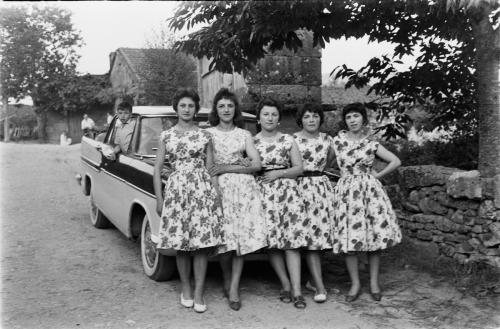 La imagen muestra a cinco chicas jóvenes, con vestidos de telas estampadas posando delante de un coche grande. Pulse para ampliar.