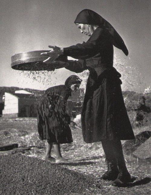 La imagen muestra dos mujeres tamizando grano. Pulse para ampliar.