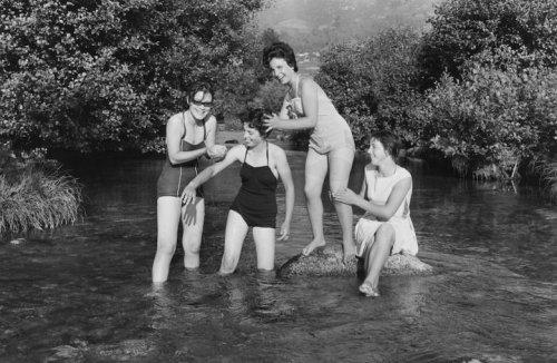 La imagen muestra a cuatro chicas jóvenes, tres en bañador y otra con vestido que están metidas en el agua del río, que les llega hasta la rodilla. Ríen y juegan entre ellas. Pulse para ampliar.