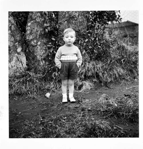 La imagen muestra a un niño muy pequeño, de unos cuatro años. Está de pie, vestido con pantalones cortos y jersey. Está muy serio y repelando, con las manos en los bolsillos como si fuera una persona mayor. Pulse para ampliar.
