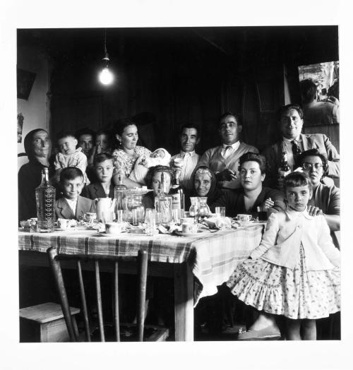 La imagen muestra un grupo familiar de 15 personas alrededor de una mesa cubierta con un mantel de plástico de cuadros sobre los que se dispone una cafetera, vasos y tazas. Todos miran hacia la cámara y una niña pequeña que está de pie en el lado derecho de la foto abre la falda de su vestido para que se vea bien. Pulse para ampliar.