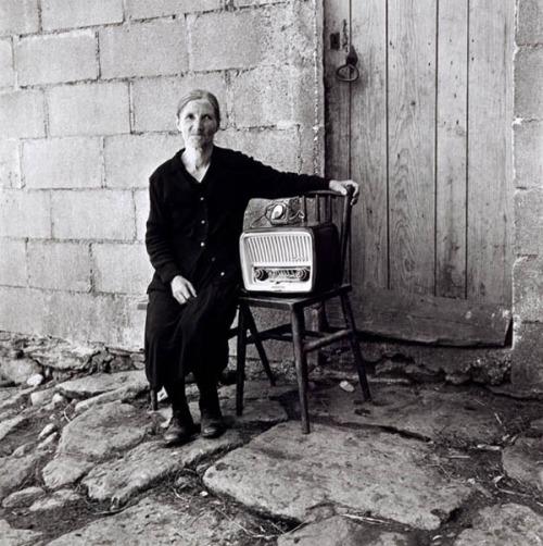 La imagen muestra a una mujer mayor, vestida completamente de negro, sentada en una silla a la puerta de su casa. A su lado hay otra silla sobre la que apoya una gran radio. la mujer pasa su brazo por el respaldo de la silla donde está la radio con gesto a medio camino entre orgulloso y protector. pulse para ampliar.