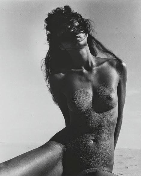 La imagen muestra una fotografía en blanco y negro de una mujer desnuda en una playa. Está sentada en la arena, apenas vemos las piernas pero sí vemos su tronco y su cabeza. Tiene el vientre y los pechos cubiertos con una fina capa de arena y su rostro está tapado por mechones de pelo que lo atraviesan. Pulse para ampliar.