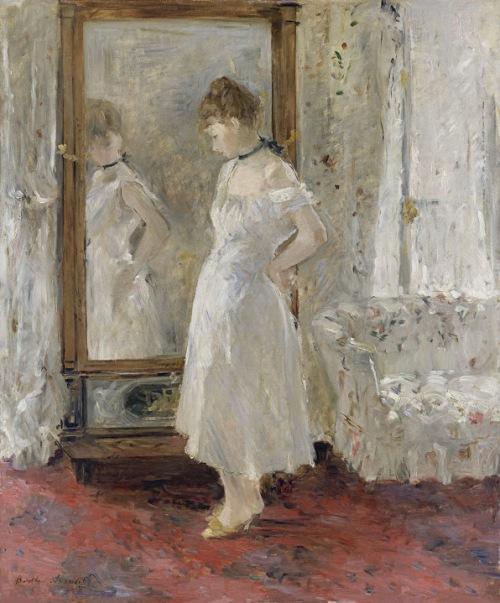 La imagen muestra el interior de una habitación en donde se ve un espejo de pie y parte de un sofá. Ante el espejo una mujer joven, vestida en ropa interior, se mira pensativa mientras lleva las manos a la espalda para abrocharse algo. Pulse para ampliar.