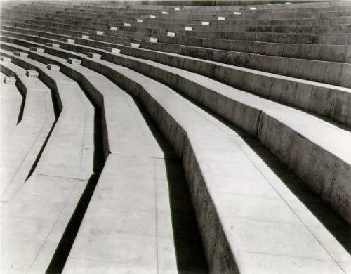 La imagen muestra un plano general de las gradas de cemento del estadio. Todo el encuadre está lleno con las gradas. El sol cae a plomo y hace que el contraste entre la claridad del cemento y la oscuridad de la sombra proyectada de las gradas cree un ritmo visual. Pulse para ampliar.