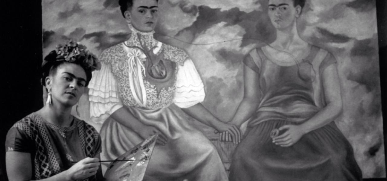 La imagen muestra a la pintora mexicana Frida Kahlo en un plano medio (cortada a la altura de la cintura) sosteniendo la paleta de pintar y un pincel. Detrás de ella, un cuadro de gran tamaño en el que aparecen dos mujeres como ella dándose la mano. la pintora mira a la cámara con la cabeza ladeada y gesto un tanto desafiante. Pulse para ampliar.