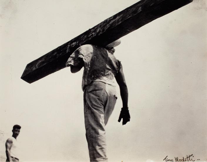 La imagen muestra, en el medio del encuadre, a un obrero de espaldas transportando una pesada viga de madera al hombro. La perspectiva hace que la viga atraviese en diagonal el encuadre mientras que el hombre traza una vertical en el medio. Pulse para ampliar.