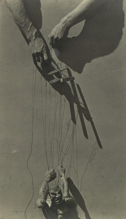 La imagen muestra un plano detalle de las manos de un titiritero que sostienen los palos con los hilos que mueven la marioneta. Los brazos del hombre caen hacia abajo, como exhaustos, mientras que la marioneta los tiene elevados hacia arriba, como en movimiento. Pulse para ampliar.