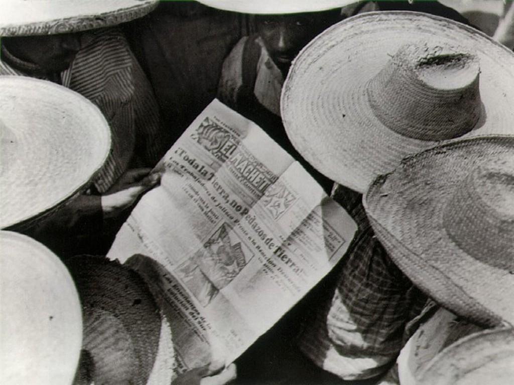 """La imagen muestra a un grupo de obreros vestidos de blanco y tocados con un sombrero mexicano de ala ancha, fotografiados desde arriba, que están rodeando a otro que sostiene en sus manos un número del periódico """"El Machete"""". Pulse para ampliar."""