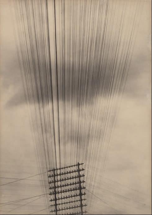 La imagen muestra una fotografía en contrapicado (tomada desde abajo) en la que se ve la parte superior de un tendido de hilos de telégrafo. Esos hilos se entrecruzan en la parte superior del poste dando la sensación de ser una trama geométrica, como la de un bastidor de tela. Pulse para ampliar.