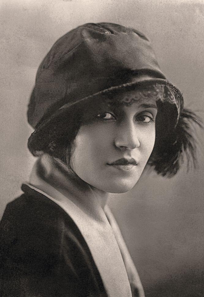 La imagen muestra un retrato en primer plano de una mujer muy joven. Está de perfil, pero gira el rostro hacia la cámara. Tiene la mirada un tanto triste y el sombrero que lleva le proyecta una pequeña sombra sobre los ojos que la hace parecer melancólica. Pulse para ampliar.