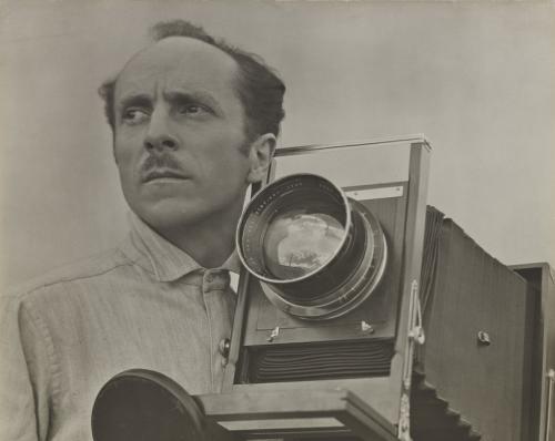 La imagen muestra un primer plano de Weston (cortado un poco más abajo de los hombros) junto a su cámara fotográfica. es un hombre ,asuro, con pelo escaso y un bigote pequeño. Mira muy serio hacia un punto a su derecha. Pulse para ampliar.