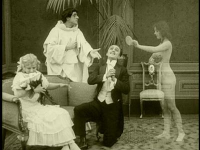 La imagen muestra un salón en el que una joven está sentada en un sillón y sostiene es sus manos un ramo de flores. La joven las huele embelesada. Ante ella y con una rodilla hincada en el suelo, aparece su enamorado, que eleva la vista al cielo con gesto feliz. Tras ambos aparece la imagen de un monje, con hábito blanco que señalando al enamorado mira a una aparición que entra en la habitación