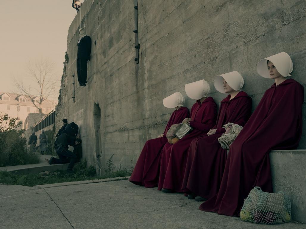 Fotograma de The Handmaid´s Tale donde se ve a las criadas descansando tras hacer la compra apoyadas en un muro de ejecución
