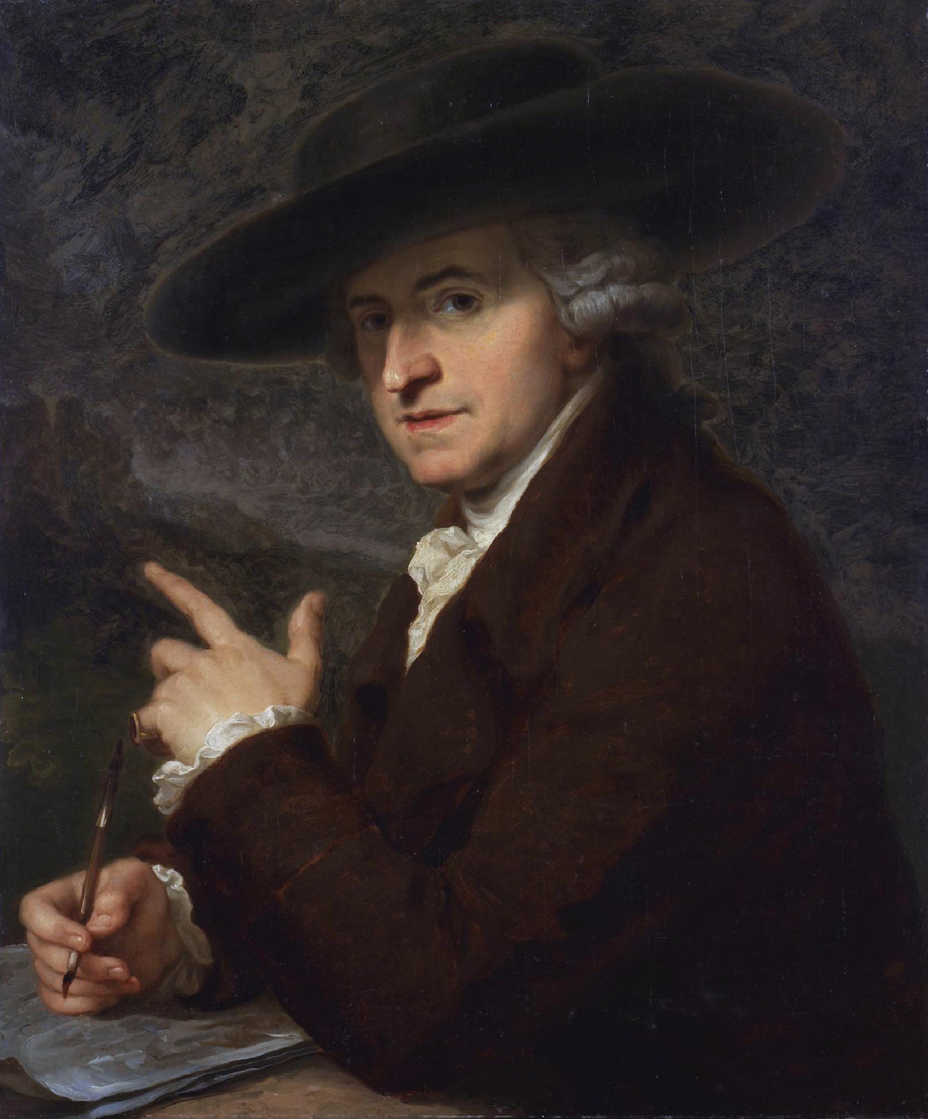 La imagen muestra a un hombre en plano medio, tocado con un sombrero que arroja una sombra sobre su mirada pero que mira al espectador con cierta curiosidad. Pulse para ampliar.